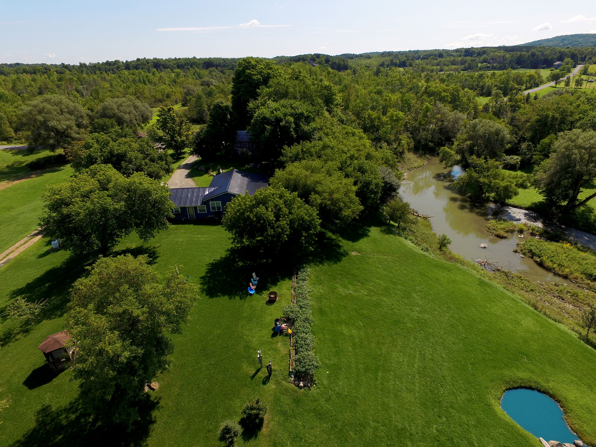 Aerial photo of backyard with creek at property in Canajoharie, New York.