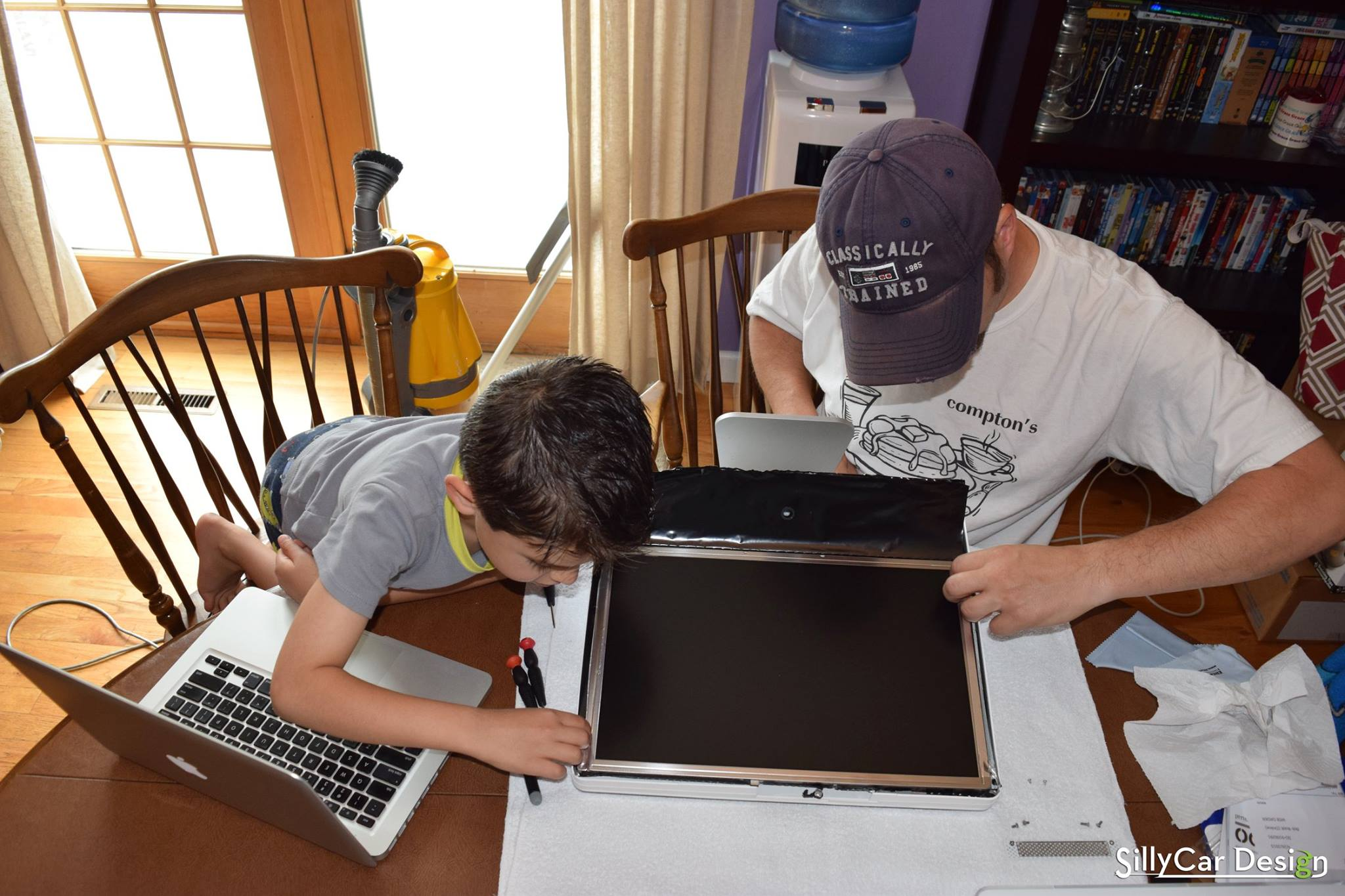 Photo of Joel and Jack Glastetter working together to repair an iMac.
