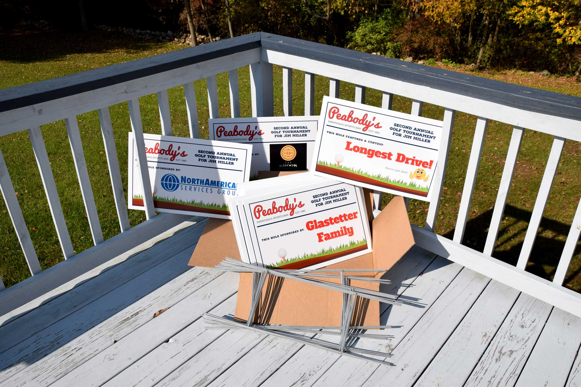 Photo of several tee signs created for Peabody's Sports Bar second annual golf tournament for Jim Miller.