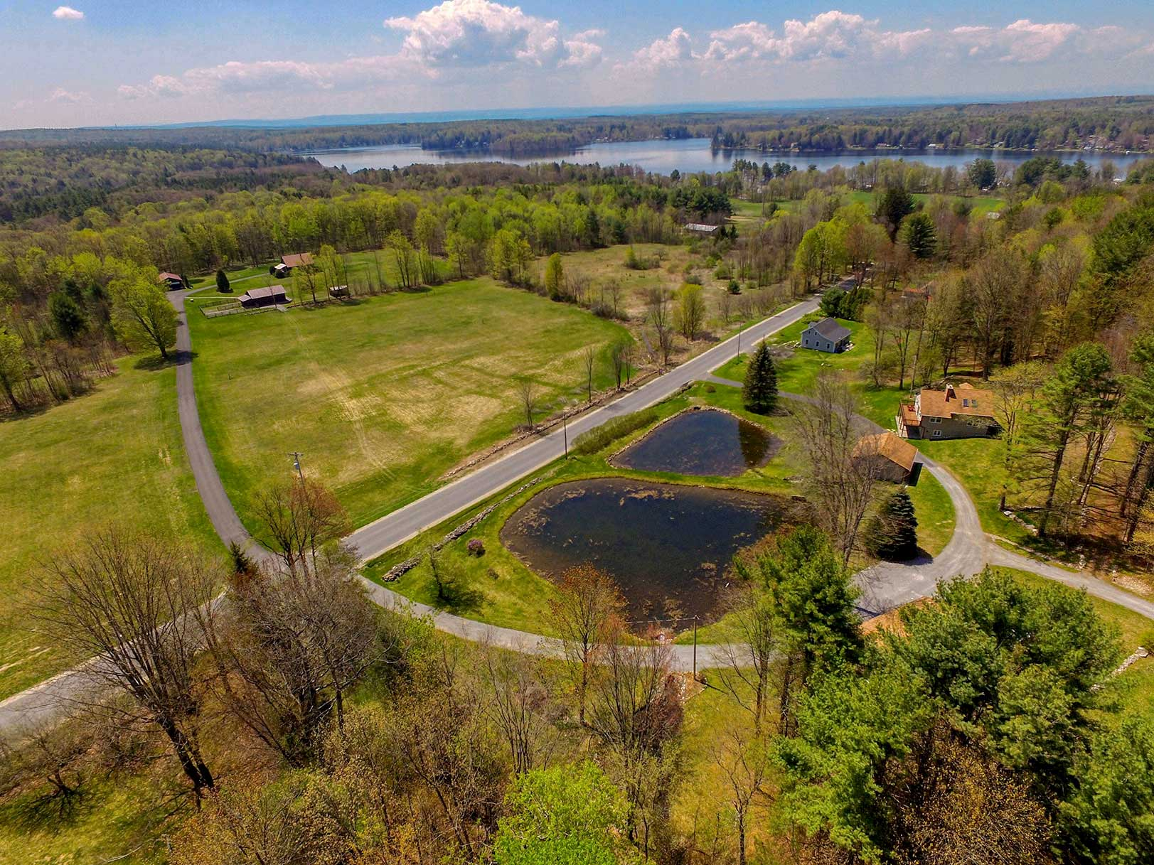 Aerial view of property with pond near Galway Lake with lake in the background.