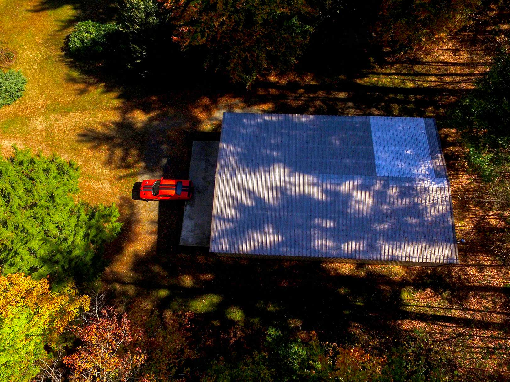 Aerial photo looking straight down over detached garage with orange muscle car in front at property in Galway, New York.