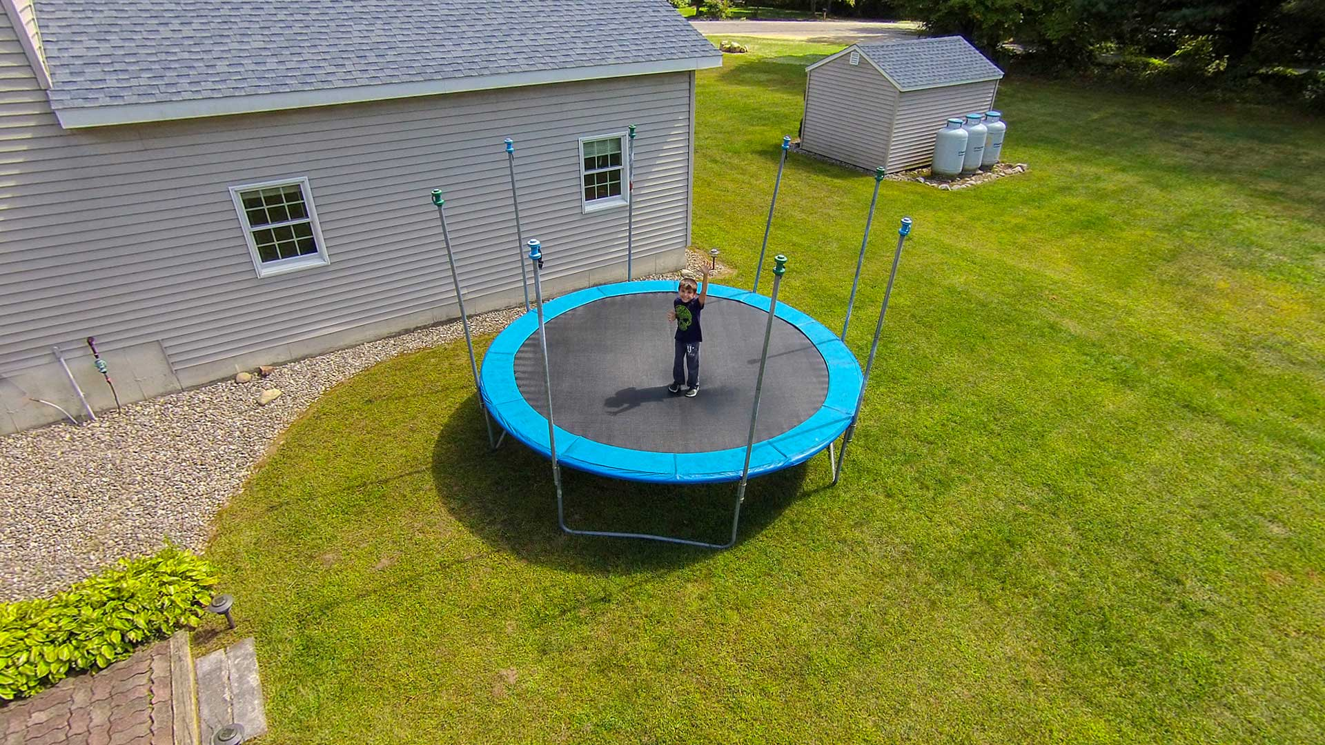 Aerial photo of young boy jumping on trampoline in backyard.